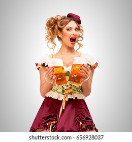 Beautiful Oktoberfest waitress wearing a traditional Bavarian dress dirndl, holding beer mugs on grey background.