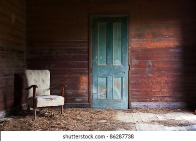 A beautiful old armchair left inside an abandoned home with red timber walls and a green door