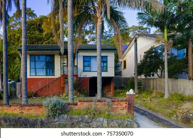 Beautiful Old Australian Suburban Houses. Street scene with brick and wooden building exterior, driveway and garden with trees at Brookvale, Sydney, New South Wales, Australia