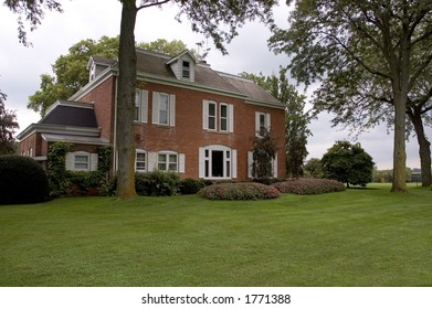 Beautiful old  brick home featuring some landscaping and lawn.