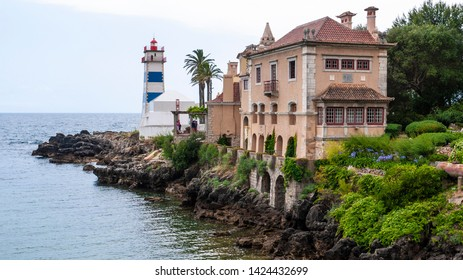 Beautiful old building on a rocky coast with a blue and white lighthouse on a cloudy summer day with trees & flowers.