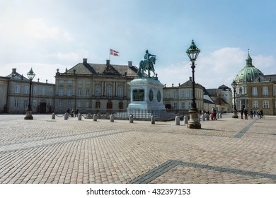 Beautiful old buildings of Amalienborg castle with the equestrian statue in Copenhagen city center at summer day, Denmark. Amalienborg castle in Copenhagen, Danmark. Old Copenhagen city center.