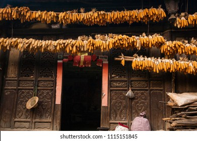 Beautiful old charming Chinese house, beautiful art wooden texture, corn drying hanging over the door. Chengzi Village, The ancient village of Yunnan, China. Village tourism.