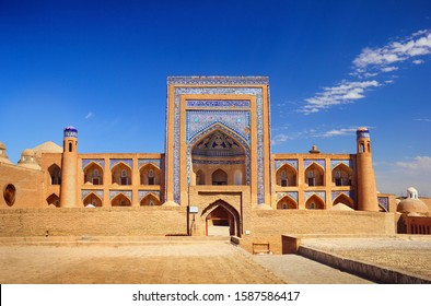 Beautiful old city view, ancient Allakuli Khan Madrassah (Allah Quli Madrasa), at the background of bright blue sky in Historic Center of Khiva (UNESCO World Heritage Site), Uzbekistan, Central Asia