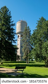 Beautiful old concrete water tank tower on a hill with green grass and trees and clear blue sky, and an empty park bench in the foreground.