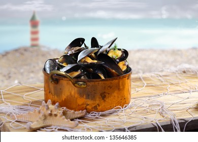 Beautiful old copper pot brimful of cooked mussels standing on old wooden boards covered with a net alongside the coast with a lighthouse visible in the distance
