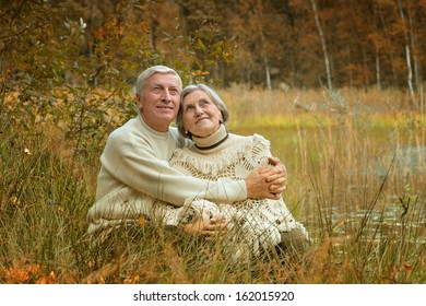 Beautiful old couple sitting in the grass near the lake. Vintage photo