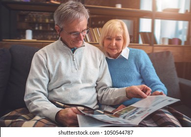 Beautiful old couple are sitting on the couch together and reading a big newspaper. Man is using reading glasses. They look concentrated and consious.