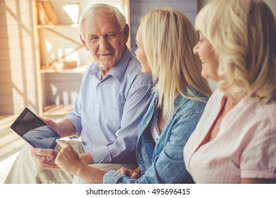 Beautiful old couple and young girl are using a digital tablet, talking and smiling while sitting on couch at home