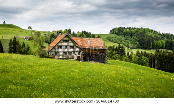 Beautiful old farm house midst the Swiss alps with a beautiful gras and sky landscape