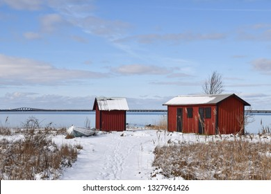 Beautiful old fishing cabins by Farjestaden at the swedish island Oland with the Oland bridge in the background