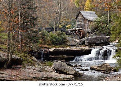Beautiful old Glade Creek Mill at Babcock State Park in the autumn season also showing the waterfall and mill pond below the mill