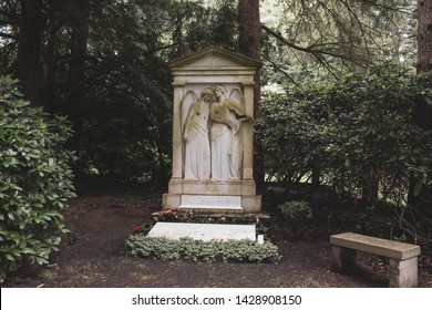 Beautiful old gravestone in peaceful environment, angel playing violin, seen in Hamburg Ohlsdorf, the world´s biggest garden cemetery, copy space for text