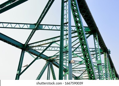 A beautiful old green bridge with steel structures.