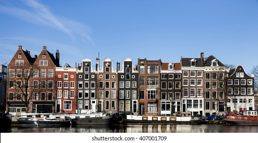 Beautiful old houses in spring on the canal with houseboats in Amsterdam, the Netherlands in black and white