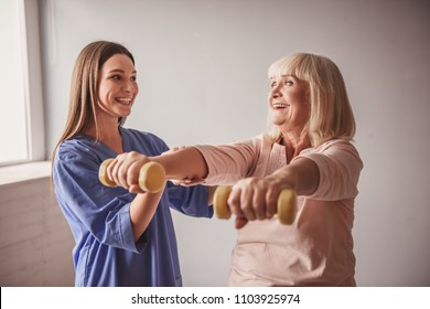 Beautiful old lady is doing exercises with dumbbells and smiling, in hospital ward. Attractive nurse is helping her