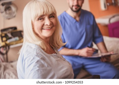 Beautiful old lady is looking at camera and smiling, in hospital ward. Handsome doctor in the background