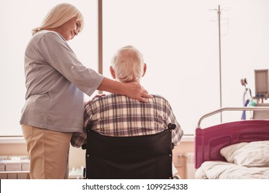 Beautiful old lady is stroking her husband and smiling while he is sitting in the wheelchair in hospital ward