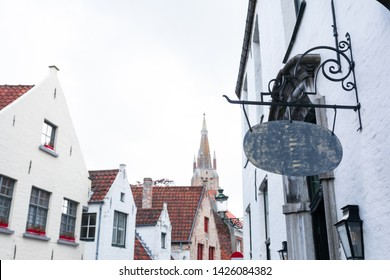 Beautiful old oval signboard on the facade in the historical center of Bruges against the background of traditional Flemish houses, Belgium