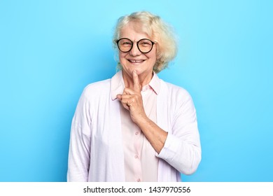 Beautiful old positive woman in glasses with a finger on her chin. successful idea.secret. gossip. isolated blue background.