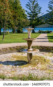 Beautiful old stone fountain in park near lake