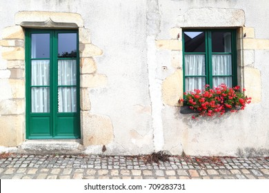 Beautiful old stone house with a green door and window full of flowers