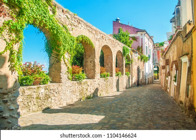 beautiful old stone wall with arches and flowers on old european street, Ravello, Amalfi coast, Italy