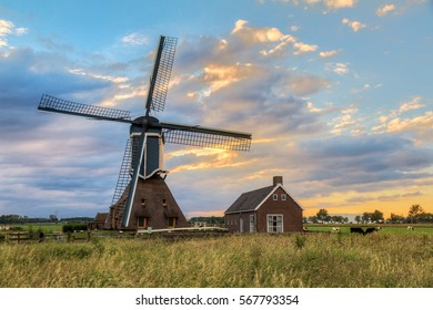 Beautiful old traditional Dutch windmill in the polder with a colorful sunset cloudscape in spring in the Netherlands