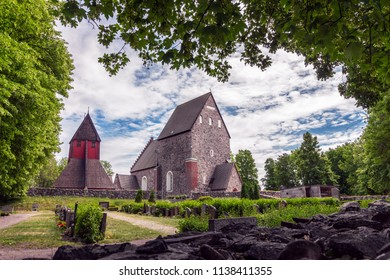 Beautiful Old Uppsala Church, outside of Uppsala Sweden (70 km from Stockholm). Gamla Uppsala Kyrka in swedish. Stone church, 13 century, and the red wooden Bell Tower. Cemetery on the foreground.