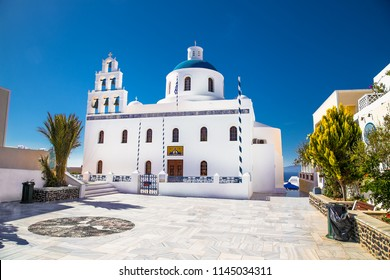 Beautiful old white ortodox church in sunny day with blue sky in Oia on Santorini island. Santorini is romantic place, one of the most visited Greek island.