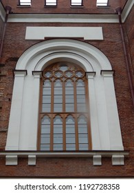 Beautiful old window in the Gothic style on the wall of red brick