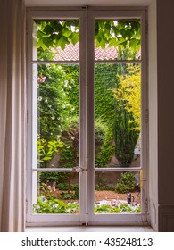 beautiful old window towards courtyard with flowers