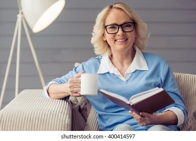 Beautiful old woman in casual clothes and glasses is reading a book, holding a cup and smiling while sitting in armchair at home
