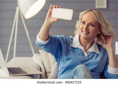 Beautiful old woman in casual clothes is making a selfie using a smart phone and smiling while sitting on couch at home