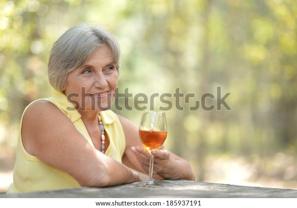 Beautiful old woman drinking wine in nature