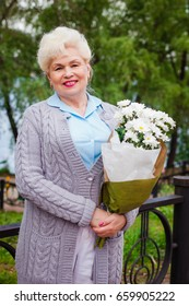 Beautiful old woman standing in a park with a bouquet of flowers