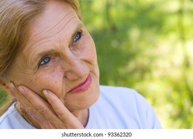beautiful old woman walking in a park