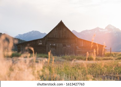 Beautiful old wooden barn with mountains in the background at sunset