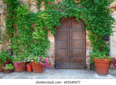 Beautiful old wooden door decorated with flowers from the medieval town, Tuscany, Italy