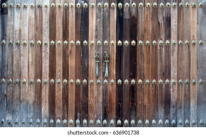 Beautiful old wooden door with iron knock ornaments and a couple of birds  metal handle
