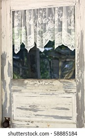 Beautiful old wooden door with peeling white paint and lacy curtains