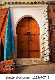 Beautiful old wooden door surrounded by moroccan berber carpets.