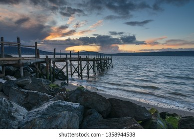 Beautiful old wooden jetty Holywood, Co Down, N Ireland during stormy weather and the setting sun