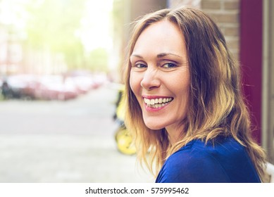 Beautiful older, middle aged woman is happy and laughing on a sunny day in a European city. Wearing a blue dress. A blurred background, space for copy. A vintage, yellowish feel to it.
