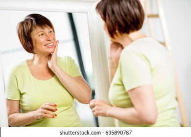 Beautiful older woman looking at her face with a smile into the mirror