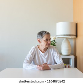 Beautiful older woman with short grey hair sitting at table in apartment (selective focus)