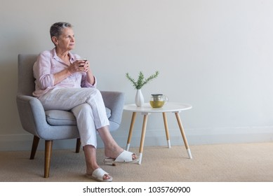 Beautiful older woman sipping tea in retro armchair looking pensive against beige wall