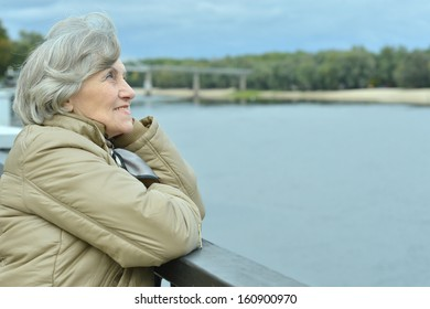beautiful older woman walking in the park alone
