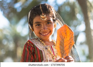 Beautiful Omani girl in traditional dress is playing in the park in Oman