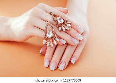Beautiful ombre manicure with earrings. French nail design. Woman holding jewellery on beige background. Fashion concept
